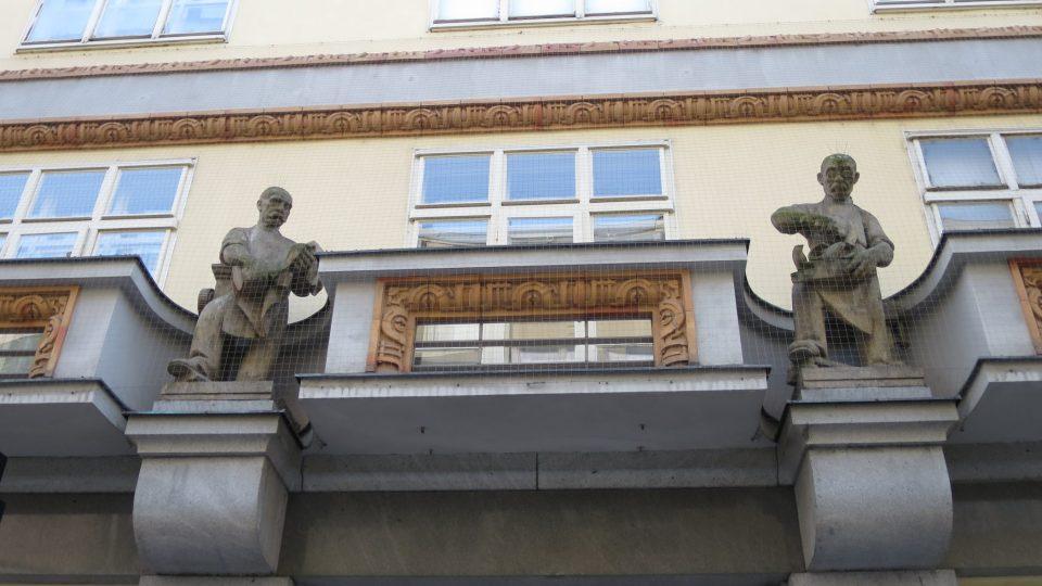 Průčelí Machoňovy pasáže zdobí čtyři sochy, na snímku textilák a truhlář