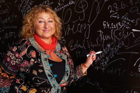 Halina Pawlowská se podepisuje na stěnu v radiokavárně Českého rozhlasu Hradec Králové