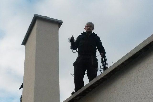 Kominík Jakub Kůta pracuje na střeše