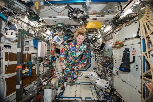 Americká astronautka Kate Rubinsová během svého minulého pobytu na ISS v roce 2016 je oblečená v pracovním overalu,  který pomalovali onkologicky nemocné děti z Anderson Cancer Center v Houstonu | foto: NASA