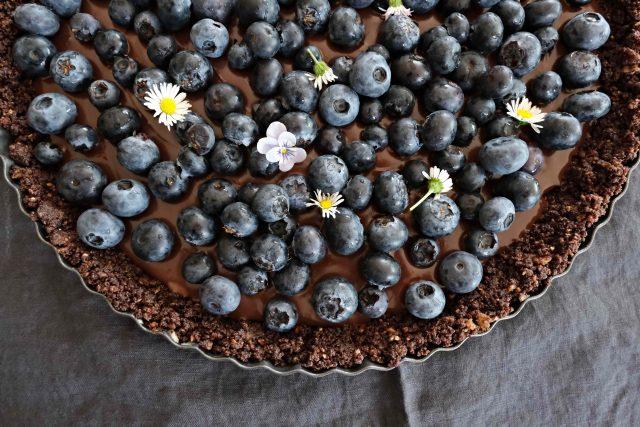 Luční i zahradní kvítka oživí čokoládový borůvkový nepečený dort.